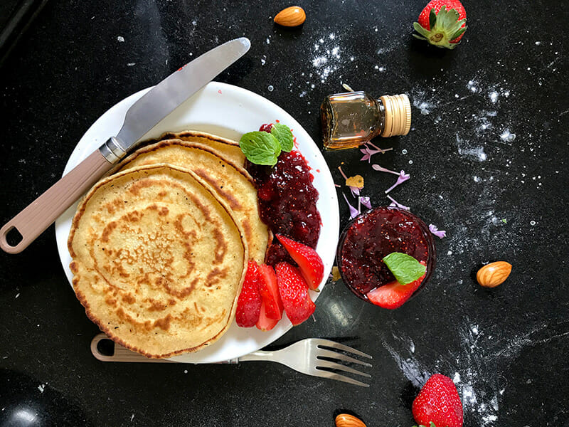 A stack of pancakes featuring strawberries and jam served on a plate with a fork and knife